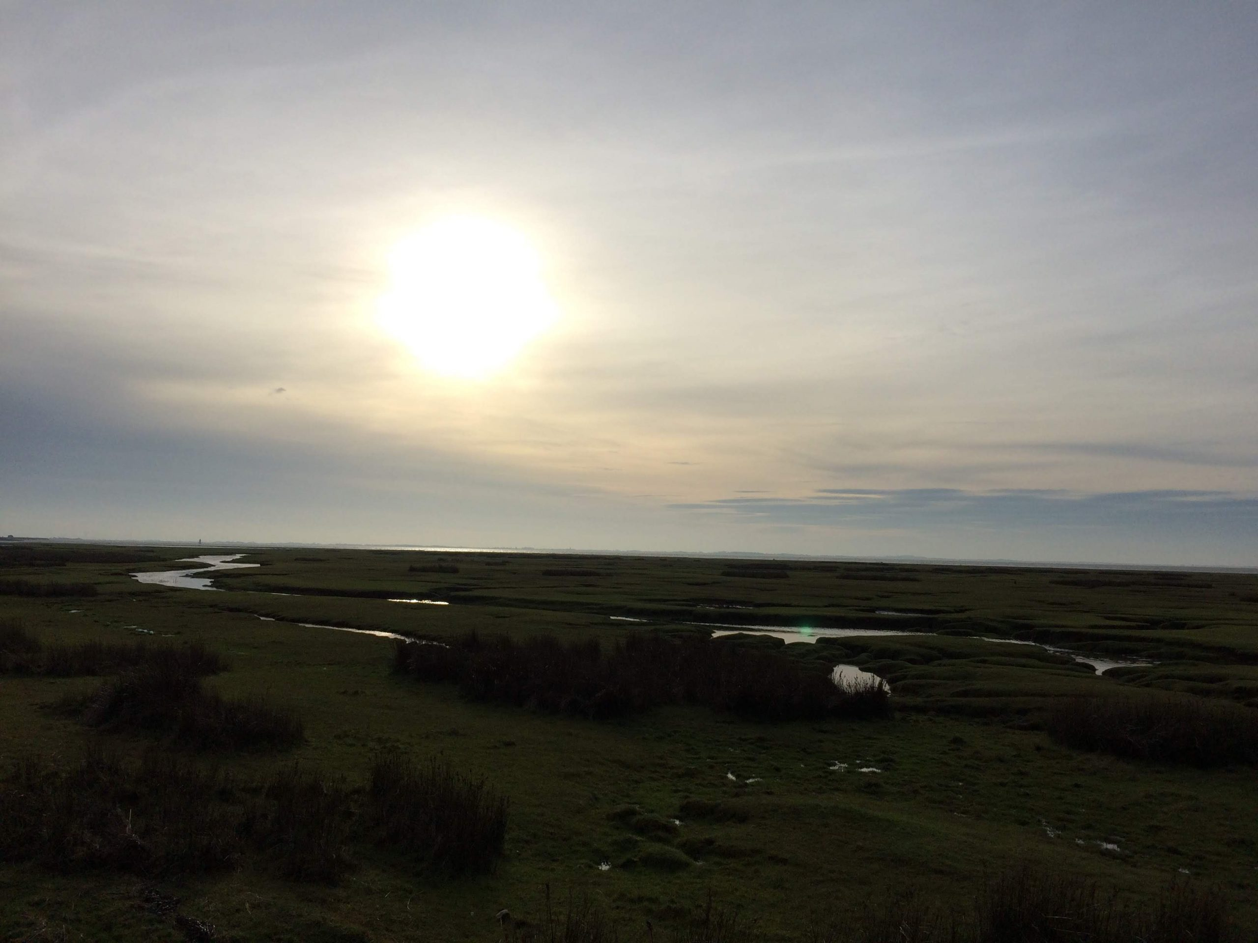 The sub shining through clouds over a wetlands marsh, Sunderland Point, Lancashire